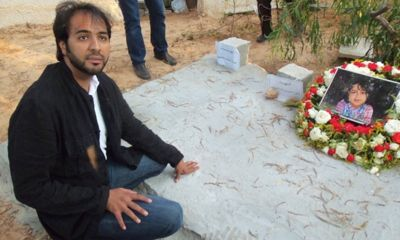 Khalad Hamedy kneels before the fresh grave of his wife, children and grandchildren